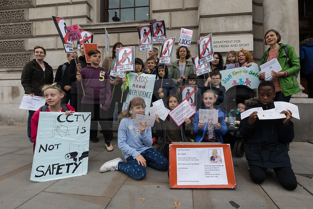 """© Licensed to London News Pictures. 24/07/2017. LONDON, UK. Primary school children from Barnet take part in a """"Don't lock us out of our library"""" protest outside the offices of the Department for Culture, Media and Sport in Westminster, delivering 440 postcards addressed to Karen Bradley, the Culture Secretary, demanding a reinstatement of independent access to libraries. Public libraries in Barnet have been shut and are now reopening with restricted access and opening hours, making the service less accessible to vulnerable members of the community. Photo credit: Vickie Flores/LNP"""
