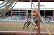 Spectators stand as the United States flag is brought into the arena before the start of the CPRA Rodeo at the Boulder County Fairgrounds on Sunday. Go to timescall.com for more photos.<br /> <br /> Matthew Jonas / Staff Photographer Aug. 2, 2015