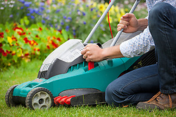 Raising the height of blades on a rechargeable electric lawnmower