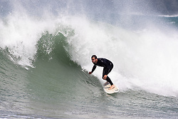 © Licensed to London News Pictures. 23/05/2020. Padstow, UK. A surfer catches a wave near Padstow, Cornwall. There is currently no RNLI Lifeguard service in the county due to Coronavirus (Covid-19). The county has experienced unusual combination of large swell and warm weather during the bank holiday weekend. Photo credit : Tom Nicholson/LNP