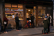 People queue outside a shop in Broadway Market during the second coronavirus national lockdown on November 7th 2020 Hackney, East London, United Kingdom. Coffee shops are only allowed to sell and serve coffee out of the house according to lockdown restrictions. The UK Government introduced a 4 week lockdown from November 5th - December 2nd to combat the coronavirus outbreak. It is the third day of the national lockdown and restrictions mean that people are only allowed to meet outside, in pairs and only if keeping social distance. Only if they already live together or have formed a social bubble can they interact freely.