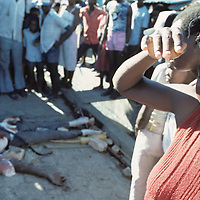 Haiti, Port-au-Prince, Woman shields eyes by battered body of security guard killed in Cite Soleil during electoral violence
