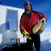 """ANTARCTICA, Queen Maud Land.  Mike Sharp, manager of Adventure Networks """"Blue 1"""" expedition base, bakes bread over barbeque near ice runway."""
