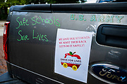"""24 JULY 2020 - DES MOINES, IOWA: A sign on the back of an Iowa teacher's pickup truck. Hundreds of teachers from across Iowa came to the state capitol Friday to protest Governor Kim Reynolds' order that school must reopen with in person education and minimized the potential for """"distance learning."""" The event was one of the largest COVID-19 protests in Iowa since the pandemic started, more than 740 teachers signed up to attend the protest. After the protest officially ended, many teachers left the capitol and drove to Gov. Reynolds' residence, where they drove around her mansion and honked horns. Some people left notes on the entrance to the governor's residence. Gov. Reynolds ordered the school reopening last week, but according to teachers, the state has not implemented health guidelines or bought protective equipment like face masks in the quantity required to slow the spread of the Coronavirus (SARS-CoV-2). Iowa's numbers of COVID-19 infections are up statewide.           PHOTO BY JACK KURTZ"""