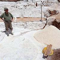 An elder man has scraped the dry salt from the surface of a pool.