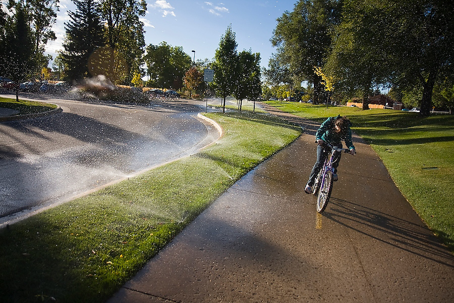 A female student is sprayed by water sprinklers as she rides her bicycle down a bike path on the University of Colorado campus in Boulder, Colorado.