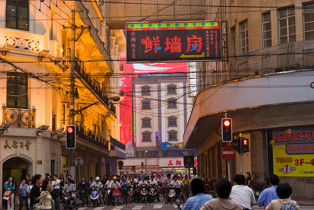 Motorcyclists wait as pedestrians cross a busy street in Shanghai, China.
