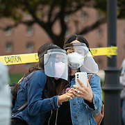 CHARLOTTE, NC - OCT 15: Two people pose for a selfie as they stand in line outside of Beatties Ford Library off Beatties Ford Road on the first day of early voting in Charlotte, North Carolina on October 15, 2020.  Early voting in the state of North Carolina runs from October 15th to October 31st. (Photo by Logan Cyrus for The Washington Post)