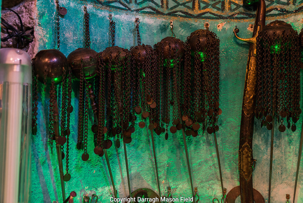 A row of Zarf needles in the Mihrab bathed in green light.