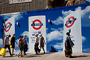 Redevelopment of Bond Street underground station in central London, UK. People pass outside a colourful hoarding covering one of the exits to the tube station as new escalators are being installed to improve the public transport system.