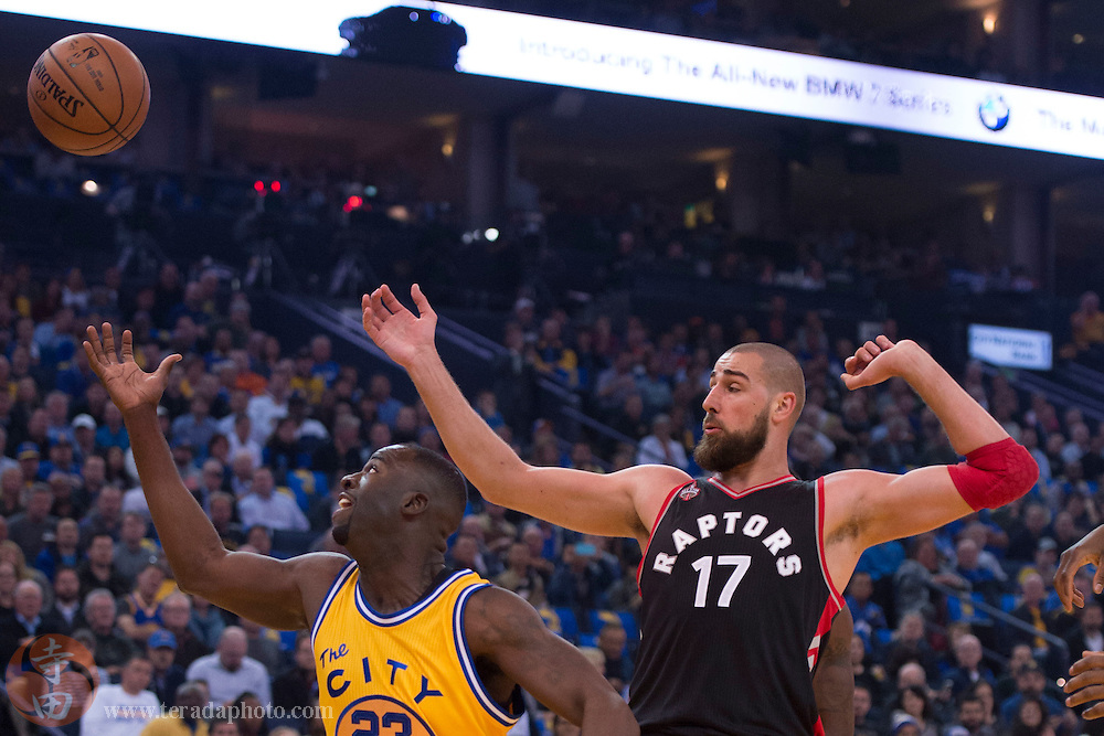November 17, 2015; Oakland, CA, USA; Golden State Warriors forward Draymond Green (23) fights for the rebound with Toronto Raptors center Jonas Valanciunas (17) during the first quarter at Oracle Arena.
