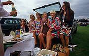 In a grass car park, six ladies await the opening of a bottle of Champagne by an unseen male friend during the day at Royal Ascot horse racing week. Surrounded by picnic hampers, trays of food and a bottle of Pimms (the gin-based cocktail drink). They are dressed in either plain or garish colours and with their long bare legs women sit at the rear of a Range Rover car. The day is overcast, with threatening clouds behind the party but despite this, they are in a bubbly and excitable mood. Royal Ascot is held every June and is one of the main dates on the sporting calendar and social season.