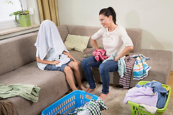 Woman with her son folding laundry in living room, Bavaria, Germany