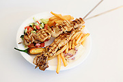 Chicken breast grilled on a skewer with chips and salad on white