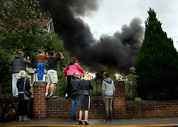© Licensed to London News Pictures. 01/09/2013. Leyland, UK Members of the public photograph the scene. The scene at Leyland St Mary's Catholic Technology College in Leyland, Lancashire as it was devastated by the blaze at 4pm yesterday (1st September 2013), which saw 100ft flames - and was tackled by 125 firefighters and 20 engines. Photo credit : Pat Tack/LNP