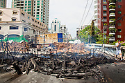 20 MAY 2010 - BANGKOK, THAILAND: A pedestrian crosses a bridge over a canal and walks past still smoldering Red Shirt barricades in the Ratchaprasong Intersection in Bangkok Thursday. The day after a military crackdown killed at least six people, Thai authorities continued mopping up operations around the site of the Red Shirt rally stage and battle fires set by Red Shirt supporters in the luxury malls around the intersection. PHOTO BY JACK KURTZ