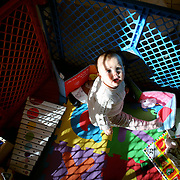 An eight month old baby girl at play in a play pen.  Photo Tim Clayton