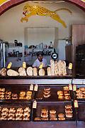 Young Mexican man in a bakery showing the bread he has for sale, San Cristobal de las Casas, Chiapas, Mexico.