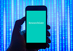 Person holding smart phone with ResearchGate   logo displayed on the screen. ResearchGate is a social networking site for scientists and researchers EDITORIAL USE ONLY