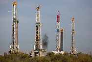 Four drilling rigs off Interstate 20, West of Midland, Texas, in the Permian Basin.