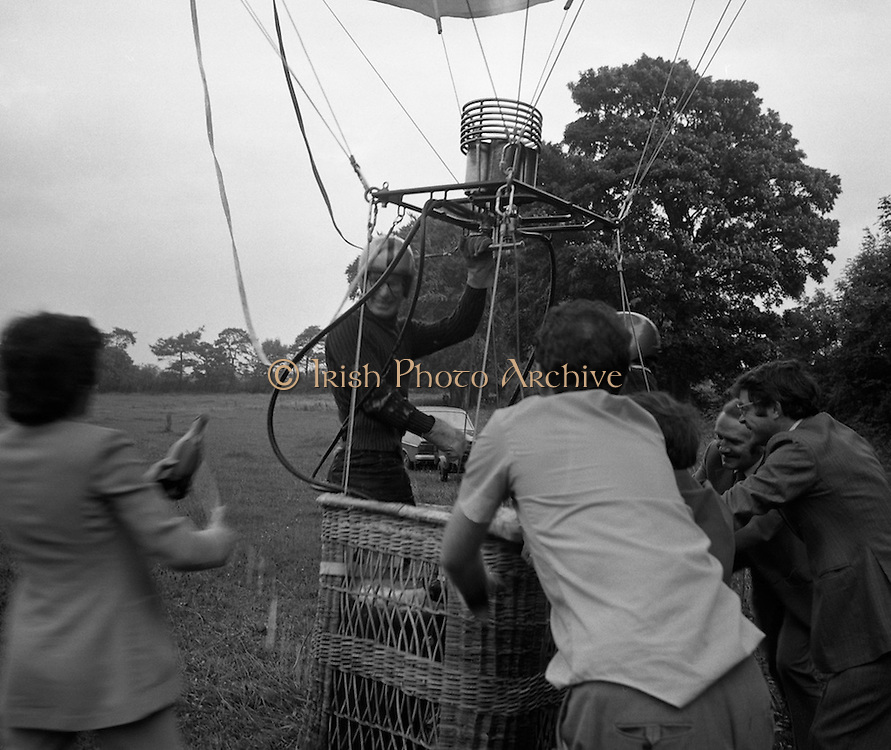 Dew Mighty Minerals Hot Air Balloon.   (H15)..1974..07.08.1974..08.07.1974..7th August 1974..The launching of the Dew Mighty Minerals hot air balloon,took place in Tullamore,Co Offaly last night,as part of the Tullamore Festival Week. The balloon was piloted by Mr Wilf Woollett,a veterinary surgeon from Loughrea,Co Galway and his co-pilot was Kevin Haugh. Miss Rosemary Mannion,the Offaly Rose of Tralee contestant sent the balloon on its way by popping a bottle of Champagne over it.  The balloon itself has a capacity of 56,000 cubic feet,is 60ft high and 50ft wide. It is made from nylon/polyproplene. The basket is 2ft square by 3ft high and carries two people,it is attached to the balloon by steel cables..Wilf Woollett has piloted the balloon in the U.S. and Britain and is a member of the Dublin Balloon Club...With the support crew hanging on to the basket,Rosemary Mannion is pictured offering a drink to pilot, Wilf Woollett.