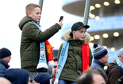 Young Manchester City fans take photos outside the stadium before the match begins