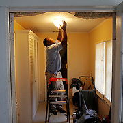 """Tarba Davis, contractor with SCE&G, secures the glass casing around a light fixture after installing new CFL light bulbs at a home in Beaufort near the intersection of Congress Street and Newcastle Street on August 28, 2014.  Charles Washington, not pictured, a renter at the home is participating in SCE&G's energy efficiency program, """"everybody in Beaufort should get on it, it helped me save some dollars,"""" said Washington.  To watch a video, go to:http://bit.ly/1gf1c6W"""