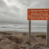 A sign warns visitors of ocean dangers at North Beach in Point Reyes National Seashore, California.