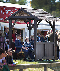© Licensed to London News Pictures. 10/05/2017. Windsor, UK. Queen Elizabeth II watches a competition from a shelter with a thatched roof at the Royal Windsor Horse Show. The five day equestrian event takes place in the grounds of Windsor Castle. Photo credit: Peter Macdiarmid/LNP