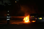 Firefighters extinguish flames in a car after an accident
