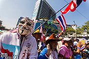 """13 JANUARY 2014 - BANGKOK, THAILAND:  An anti-government protestor  with a Guy Fawkes mask in front of MBK shopping center in Bangkok. Many of the protestors wear Guy Fawkes masks, inspired by the movie V for Vendetta. Tens of thousands of Thai anti-government protestors took to the streets of Bangkok Monday to shut down the Thai capitol. The protest was called """"Shutdown Bangkok"""" and is expected to last at least a week. The Shutdown Bangkok protest is a continuation of protests that started in early November. There have been shootings almost every night at different protests sites around Bangkok, including two Sunday night, but the protests Monday were peaceful. The malls in Bangkok stayed open Monday but many other businesses closed for the day and mass transit was swamped with both protestors and people who had to use mass transit because the roads were blocked.   PHOTO BY JACK KURTZ"""