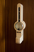 Socialist wall thermometer in preserved office of former Minister in charge of GDR secret police chief, Erich Mielke - an exhibit in 'Haus 1' the ministerial headquarters of the Stasi secret police in Communist East Germany, the GDR. Built in 1960, the complex now known as the Stasi Museum. Before the fall of the Wall, it was a 22-hectare complex of espionage whose centrepiece is the office and working quarters of the former Minister of State Security, Mielke who considered their role as the 'shield and sword of the party', conducting one of the world's most efficient spying operations against its political dissenters during its 40-year old socialist history. After the fall of the socialist state, Mielke was sentenced to 6 years in prison and died in 2000, aged 92.