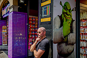 The fantasy monster Shrek and a bald man adopting the same postural echo outside a tourist trinket shop near Piccadilly Circus, on 9th May 2018, in London, England. Shrek is a 2001 American computer animated adventure fantasy comedy film loosely based on William Steigs 1990 fairy tale picture book.