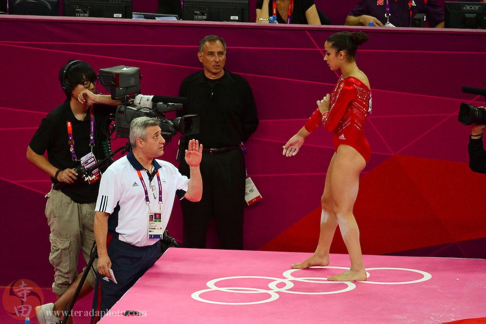 Jul 31, 2012; London, United Kingdom; USA coach Mihai Brestyan, left, instructs Alexandra Raisman (USA), right, before Raisman performed her routine in the floor exercise during the London 2012 Olympic Games at North Greenwich Arena.