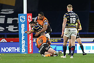 Junior Moors of Castleford tackles a Leeds Rhinos player during the Betfred Super League match between Leeds Rhinos and Castleford Tigers at Emerald Headingley Stadium, Leeds, United Kingdom on 26 October 2020.