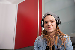 Portrait of a young man with dreadlocks and piercing listening to music with headphones, Munich, Bavaria, Germany