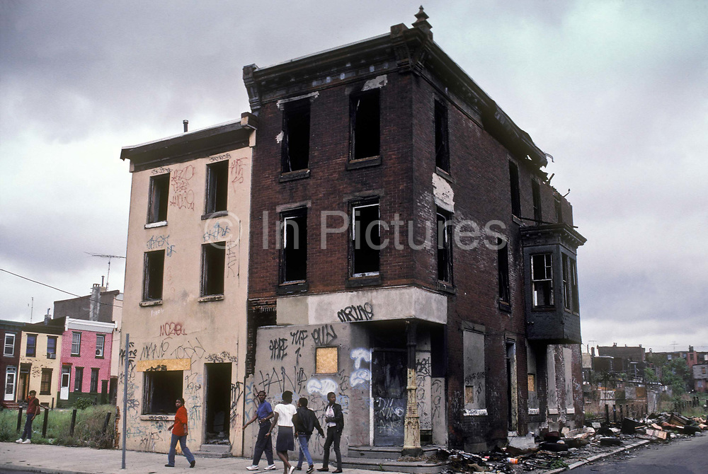 Black youth walk by the derelict and burned out remains of several buildings in a Washington DC impoverished neighbourhood, a city with a very high crime rate, USA.