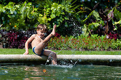 © Licensed to London News Pictures. 06/07/2013. London, UK.  A young boy splashes in the water of a fountain at Regents Park, central london, during a sunny saturday.  Photo credit : Richard Isaac/LNP