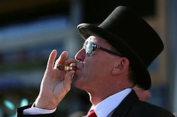 Racegoer enjoys a cigar during day three of Royal Ascot at Ascot Racecourse.