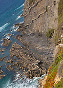 Intensely folded rock of wave cut platform at the base of a steep cliff.  Rocky rugged coastal landscape on the Rota Vicentina Fisherman's Trail long distance footpath route, near Bunheira, Aljezur, Algarve, Portugal, Southern Europe