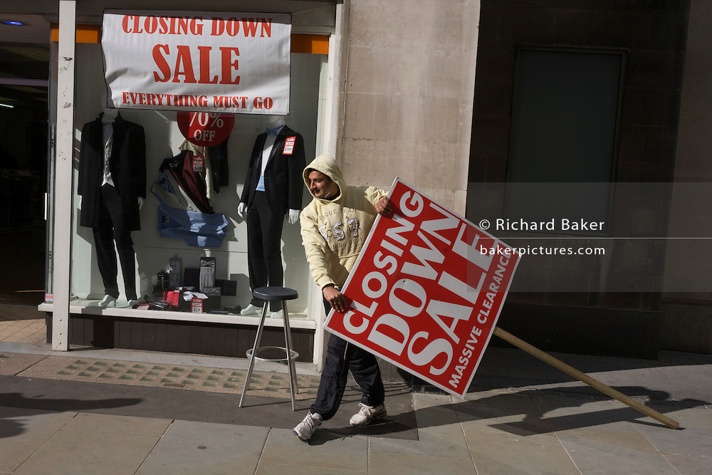 During a windy afternoon, a sandwich board man holds his broken sign for a menswear shop's closure sale in central London