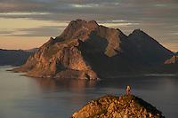 Female hiker on summit of Hornet with mountains of Vestvågøy rising across sea in distance, Flakstadøy, Lofoten Islands, Norway