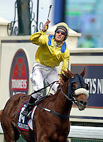 Champion jockey Damien Oliver wins the 2002 Melbourne Cup on Media Puzzle at Flemington racecourse just days after his brother Jason, also a jockey, died in a tragic training accident in Perth. On crossing the line Oliver blew a kiss and raised his whip up to the heavens in dedication to his fallen brother. It was a moment that transcended sport and made him a national hero. (Copyright Michael Dodge/Herald Sun)