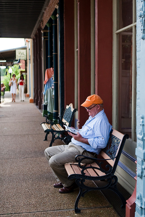 Older man reading a book on the square, Oxford Mississippi.