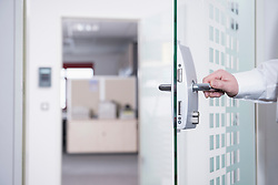 Businessman opening office door, Munich, Bavaria, Germany