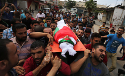 October 4, 2018 - Beit Lahia, Gaza Strip, Palestinian Territory - Mourners carry the body of Palestinian Ahmed Abu Habel, 15, who was shot dead by Israeli troops during clashes in a demonstration against Israeli blockade on Gaza Strip, and the United States decision to stop funding and backing the United Nations agency for Palestinian refugees (UNRWA), at the Erez crossing with Israel, during his funeral in Beit Lahia in the northern Gaza Strip.   (Credit Image: © Ashraf Amra/APA Images via ZUMA Wire)