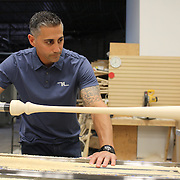 Pete Tucci, watches a baseball bat emerge from the wood lathe in his factory, Tucci Lumber Company, which makes baseball bats. Norwalk, Connecticut, USA. 27th June 2014. Photo Tim Clayton