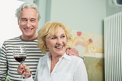 Mature couple drinking wine, smiling