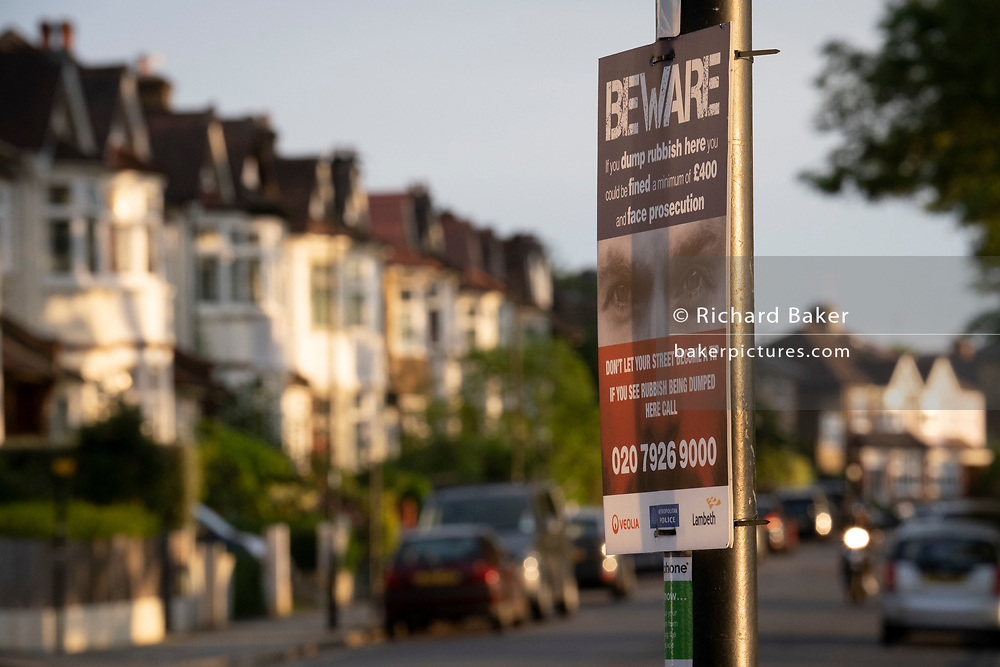 Suburban houses in evening sunshine and a Lambeth council warning sign of fines and prosecution for littering and fly-tipping, on 7th June 2021, in south London, England.