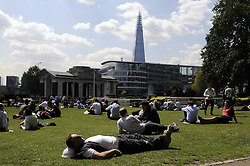 © Licensed to London News Pictures. 15/05/2014<br /> Sunny weather in London this Lunchtime (15.05.2014)<br /> City workers enjoying the midday sun in Trinity Square Gardens,Towers Hamlets,London.<br /> Photo credit :Grant Falvey/LNP